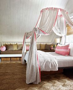 In a Bahamas house designed by Amanda Lindroth, a wrought-iron Italian Campaign Canopy bed from Anthropologie is draped with hand-printed John Robshaw fabric, trimmed in pink Norbar Sundi. Naga bed linens and Primrose pillow also from John Robshaw. Children can sleep over on the long banquette covered in a Kravet linen. - HouseBeautiful.com