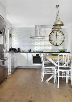Pressed metal subway tile backsplash Brushed metal chairs Oversized industrial clock Industrial pendants Perfect kitchen