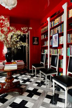 The entry triples as a dining area and library. To unify the irregular proportions of the space, Olsen used Fine Paints of Europe Hollandlac Brilliant in Tulip Red for the ceiling and walls. A trio of Louis XVI–style side chairs covered in leather adds a touch of formality. Plus: Designer Secrets for Small Spaces