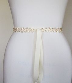 This floral off-center belt is made with sparkly Swarovski crystals and is available in gold or silver finish. The belt measures 24 long and the main crystal design measures 4 1/2 long and 3 1/2 wide. Finished with 5/8 wide grosgrain ribbon measuring 150 long. The belt comes 24 long as
