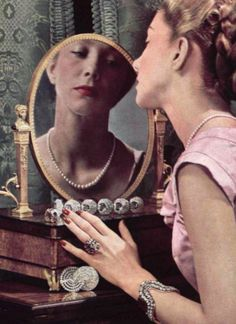 Woman looking in the mirror admiring her Dusausoy jewelry, 1947