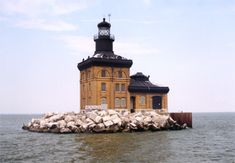 """Toledo Harbor, OH - Standing in Lake Erie, eight miles northeast of Toledo Harbor, is a distinctive lighthouse that some believe resembles a gingerbread house. While there is no witch living inside as there was in the tale of Hansel and Gretel, there is an eerie """"phantom lightkeeper"""" who for years beckoned to mariners from an upper-story window. This unique beacon, the Toledo Harbor Lighthouse, has guarded the entrance to Maumee Bay for over a century."""