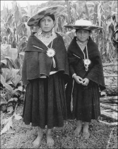Indigenous women in Saraguro, Ecuador. These Ecuadorian women display traditional, yet contemporary clothing that includes wide-brimmed woven hats with markings indicating ethnicity and pinned anakus, or wrap-around skirts and Ilikllas, or mantles. Decorative earrings and necklaces adorn them.
