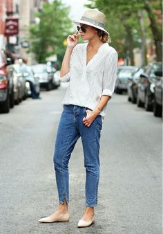 Danielle Bernstein of We Wore What wears a striped blouse, skinny jeans, pointed-toe flats, aviator sunglasses, and a fedora