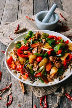 Big Plate chicken or da pan ji (大盘鸡) is popular dish of Northern China. This Chinese big plate chicken stew recipe originated in the Xinjiang, China where bold and tasty spices are cooked with chicken, potatoes, carrots and peppers served over noodles..