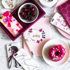 Instagram flatlay. White marble background. Props: black cherries, hot pink frosted donut, light pink notebook, and pink/white plates, illustrated phone cases. (instagram.com/thedairy)