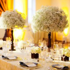 pedestals topped with baby's breath surrounded by surrounded by mercury glass votives and champagne flutes with floating candles in colored water...would love it