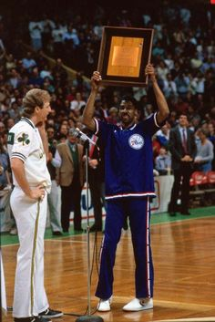 Julius Erving is presented with a plaque from Larry Bird during his last game against the Boston Celtics at the Boston Garden