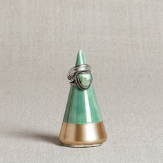 This minimalist ring holder has been handmade from porcelain, covered in a smooth, emerald green glaze, and then finished with hand-applied gold leaf. Standing nearly 3 inches tall, this modern silhouette is the perfect home for your special jewelry.  ___________________________________________________________________________  Find us on Instagram for new product sneak peeks, studio pictures, sales events, and more great info: @honeycombstudio