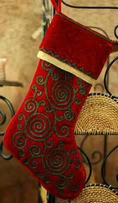 Glittering zardozi embroidery creates mesmerizing spirals on deep red velvet. Applied by hand with glittering metallic zari threads, they adorn an heirloom Christmas #stocking.