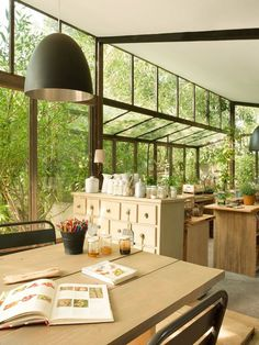 This beautiful kitchen design shares a window with the greenhouse.  The result is that those sitting in it feel that they are outside in the garden.