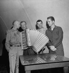 War correspondent Ernie Pyle (L) sings w. others, including actor Jackie Cooper (R) during last party before shipping out to cover the invasion of Okinawa where Pyle would be killed by a sniper. April 1945 Photographer: J. R. Eyerman