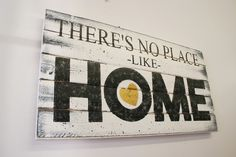 """There's No Place Like Home Pallet Sign. This is a wood pallet sign that measures 24"""" x 12"""". The background is painted Ivory. Wording is Black with a Metallic Gold heart. This piece is handpainted and sanded for a distressed/shabby chic/vintage look. It is then sealed with a water based varnish. The back is left unfinished and comes ready to hang with sawtooth hanger."""