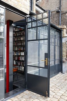 Trombe - An external shot of steel doors which have antique bronze Bauhaus style ironmongery. A modern extension with historic elements.
