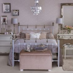 Vintage pink bedroom with metal double bed, pink velvet footstool, white wood vintage-style furniture and glass chandelier