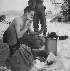 An American artilleryman shaves in frigid cold, using a helmet for a shaving bowl, during the Battle of the Bulge.