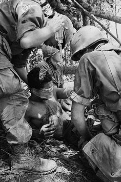 """A Shau Valley, South Vietnam --- Medics tend to a wounded American airborne trooper after he was felled by an enemy hand grenade while storming """"Hamburger Hill"""" may 18.  GIs nicknamed the mountain in the northern a Shau Valley """"Hamburger Hill"""" because of the bloodshed over it. --- Image by © Bettmann/CORBIS"""