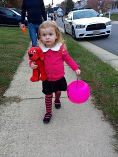 Emily Elizabeth Halloween costume with Clifford The Big Red Dog. The socks are just leg warmers pulled down. The rest is a pink cardigan overtop a long sleeve black DRESS with a white collar attached to it.