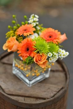 Centerpiece of peach roses, orange gerber daisies, green mums and white asters in silver cube wrapped in peach beaded wire