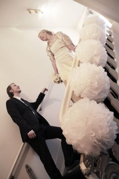 Decorate the banisters of stairs with large white pom poms for a romantic feel and a beautiful back drop for photos too.