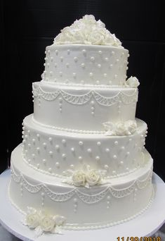 White swags, dots and roses decorating a four layer cake