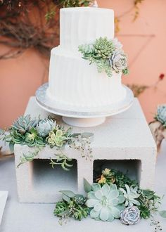 White layer wedding cake and simple succulent cake toppers on a concrete block cake stand