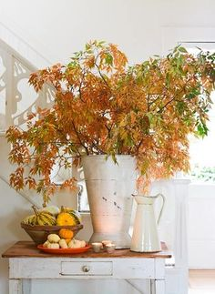 Now that fall is officially here, rustic antique vases and bowls paired with changing fall foliage and pumpkins create an amazing centerpiece for your home decor.   [Helen Norman Photography]