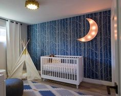 For an avid outdoorsy couple expecting their first baby, this adorable nursery is a dream come true. Using as inspiration the parents' many camping and hiking trips, the designers filled one accent wall with an ethereal forest scene and added a cozy teepee hideout.