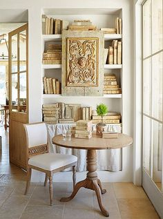 Plaster shelves with antique books and round pedestal table modern farmhouse neutral European antique style Patina Farm Giannetti Home