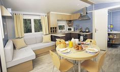 Love this bright, airy yellow and blue mobile home kitchen/dining area.
