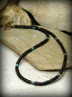 A mens necklace beaded with dark pen shell tube beads and kingmans turquoise heishi separated by ethiopian copper heishi. I love the dark rich