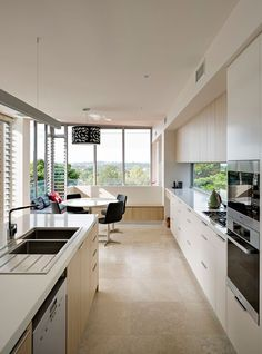 A minimalist kitchen featuring light wood and white cabinetry, simple and understated hardware, and expansive views.  How do you like the window backsplash? Design by http://www.basearchitecture.com.au/