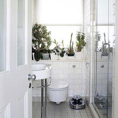 Vasos com plantas quebram o tom monocromático do banheiro branco.  Fotografia: http://decoholic.org