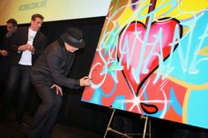 "Carlos Santana and muralist John ""Crash"" Matos sign artwork created by Crash to be sold at auction benefitting Milagro Foundation during the HBO Latino NYC Premiere of ""Santana: De Corazon"". (Photo by Jerritt Clark/Getty Images for HBO Latino)"