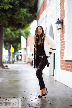 ipped black jeans will add edge and individuality to any outfit. Aimee Song wears a pair with a cute black blouse and a furry coat; a signature winter style. Jacket: H&M, Jeans: Paige Denim, Blouse: Anine Bing, Pumps: Saint Laurent.