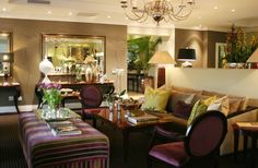 Sophisticated, glamorous interior design and decoration of a boutique hotel in Johannesburg.  Lounge area with colourful upholstery and creative accessories.