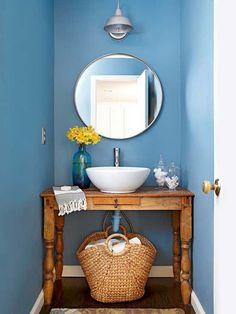 plan vasque en bois naturel miroir rond et peinture murale en bleu