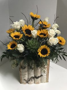 Extra large arrangement for baby shower party using a rustic wood container, succulents, sunflowers, roses, & an assortment of greens