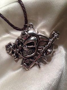 Collar realizado en cordón simil cuero marrón, con pieza central metálica en forma de calavera pirata.