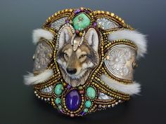 Cuff   Heidi Kummli.  Beautiful porcelain timber wolf is made by artist Laura Mears combined with spoon handles, turquoise, jade cabochon dyed purple, fur, river stones and lots of seed beads.