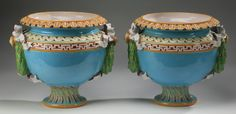 Pair of Minton majolica 'Laurel Leaf' jardinieres, circa 1876,  having flared scalloped rims above turquoise bodies with a band of cabochon and with sea scrolls and Greek key designs at the shoulders flanked by laurel leaf wreath, ribbon, and bow handles, each rising on circule pedestal bases decorated with spiral fluting, Minton shape no.766.