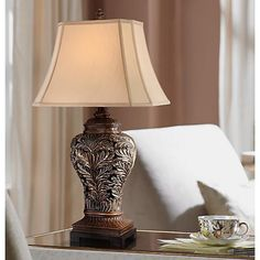 This enchanting table lamp has a beautiful openwork vase design of gently curling leaves. A wonderful lighting accent for the living room or family room.