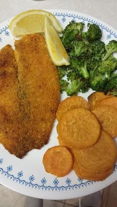 Parmesan crusted tilapia that's 21 Day Fix approved :) lightly coated with olive oil, breading: 3/4 cup parmesan, 2 tsp paprika, and a dash of sea salt. enough to coat 3 fillets. Made with roasted broccoli and sweet potatoes. Garnish with lemon wedges for fish and broccoli.