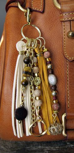 This handmade tassel charm can be used on your purse, backpack, zipper, wherever youd like to add some charm! Its made up of matte gold plated chain, gold plated charms, and different types of beads - tigers eye, soap stone, wood, brass, glass. The suede tassels are cream and camel in color. It is approximately 6.25 long.