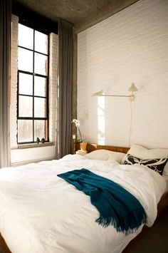 white brick wall bedroom and those windows!
