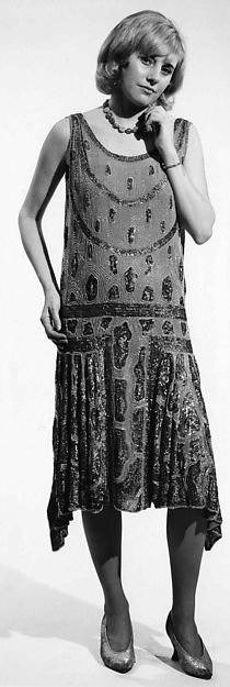 During the 1920s, nightlife ruled over the day.  Men and women dressed for an evening out, filled with dinner, cocktails and dancing.  Dress for women changed dramatically, as hemlines rose and waistlines dropped, creating a tubular silhouette