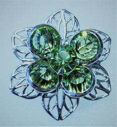 E-174, $3.99, A Beautiful Silver Toned Flower with Green Swarovski Crystals in the Center