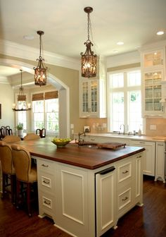 Butcher block island with the cream cabinets. Love this