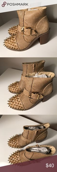 Beige Spike Ankle Booties  Step out in style to your next night on the town! Pair these hot booties with leggings or a chic LBD for an edgy look! This style features a texture faux crock upper with a high polished Spike and buckle accent, almond closed toe, side zipper closure, stitched, smooth lining, and finished with a cushioned foot bed. Approximately 3 inch heels. Liliana Shoes Ankle Boots & Booties