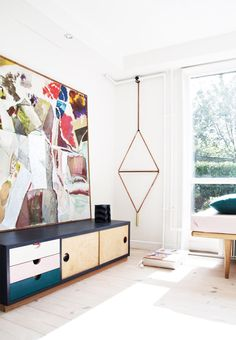 Hanging wall art with oversized painting, console table and white walls in living space